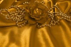 Rosa y perlas de oro en el satén Fotos de archivo