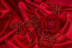 Rosa y perlas del rojo en el satén Fotos de archivo libres de regalías
