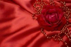 Rosa y perlas del rojo en el satén Fotografía de archivo libre de regalías