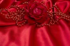 Rosa y perlas del rojo en el satén Imágenes de archivo libres de regalías