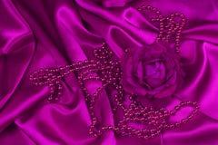 Rosa y perlas del rosa en el satén Foto de archivo libre de regalías