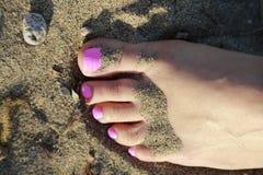 Rosa Zehen, die auf dem Strand stillstehen Stockfotografie
