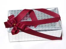 Rosafarbene Beschaffenheit der silbernen Geschenkbox mit dem roten Band, lokalisiert Stockbilder