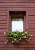 Rosafarbene Blumen im braunen Fenster Stockbild