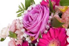 Rosafarbene Blumen mit weißen Perlen Stockfotografie