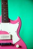 Rosafarbene Gitarre getrennt auf Grün Lizenzfreies Stockbild