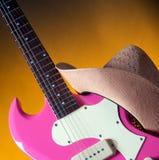 Rosafarbene Gitarre und westlicher Hut Lizenzfreie Stockbilder