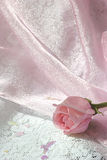 Rosafarbene Knospe des Rosas auf glänzendem rosafarbenem Tulle über weißem lace2 Stockfoto