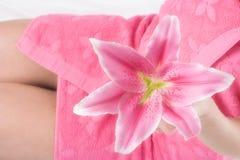 Rosafarbene Lilie in der Frauenhand auf rosafarbenem Tuch Stockfotografie