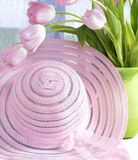 Rosafarbene Mütze und Tulpen im Vase stockbild