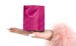 Rosafarbene Papiertüte an Hand. Lizenzfreies Stockbild