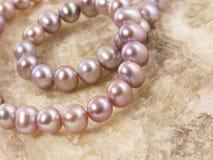Rosafarbene Perlen auf einem Stein Stockbilder