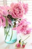 Rosafarbene Pfingstrosen im Glasglas stockbilder