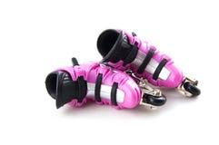 Rosafarbene Rollerblades, die auf ihre Seite legen Stockfotografie