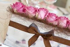 Rosafarbene Rosen auf der Hochzeitstabelle Stockbild