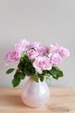 Rosafarbene Rosen auf grauer Wand Lizenzfreie Stockbilder