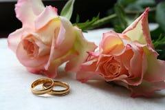 Rosafarbene Rosen mit Hochzeitsbändern Stockbilder