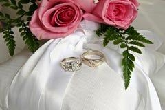 Rosafarbene Rosen und Hochzeitsringe Stockfoto