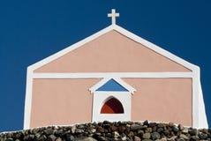 Rosafarbene Santorini Kirche auf einem Abhang Stockfotos
