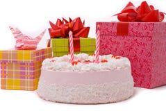 Rosafarbene Torte mit zwei Kerzen und Geschenken in den Kästen Lizenzfreie Stockbilder