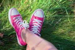 Rosafarbene Turnschuhe auf Mädchenfahrwerkbeinen Stockbilder