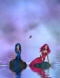 Rosafarbene und blaue Nixen, die auf Felsen sitzen Stockfotos