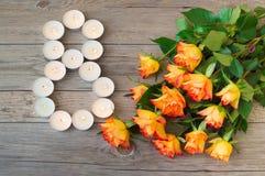 Rosafarbene und kleine brennende Kerzen der Orange in der Form nummerieren 8, acht auf hölzernem Hintergrund Glücklicher internat Stockbilder