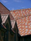 Rosafarbene und rote Flieseschindeln auf einem Dach Stockbild