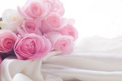 Rosafarbene und weiße Rosen, die in Seide mit Hintergrundbeleuchtung legen Stockbild