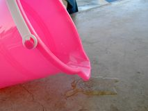 Rosafarbene Wanne, die Wasser für Sommer verschüttet Lizenzfreie Stockfotos