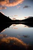 Rosafarbene Wolken und noch See lizenzfreies stockfoto