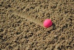 Rosafarbener Golfball in einem Bunker Lizenzfreie Stockbilder