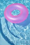 Rosafarbener Ring, der in ein blaues Pool schwimmt lizenzfreies stockfoto