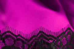 Rosafarbener Satin mit schwarzer Spitze Stockfotos