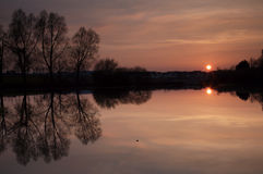 Rosafarbener Sonnenuntergang über See Stockfotos