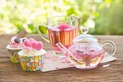 rosafarbener Tee mit Teetopf im Garten Stockfotografie