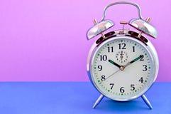 Rosafarbener und blauer Hintergrund der Alarmuhr - stockbilder