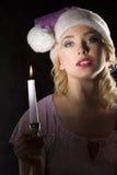 Rosafarbener Weihnachtsmann in der Dunkelheit mit Kerze Stockfotos
