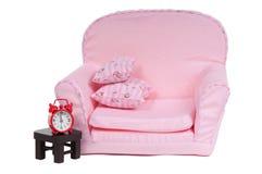 Rosafarbenes artchair mit der Tabelle und Alarmuhr getrennt Lizenzfreies Stockfoto
