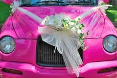 Rosafarbenes Hochzeitsauto mit Blumenstrauß der Blumen stockbilder