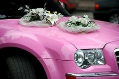 Rosafarbenes Hochzeitsauto mit einem Blumenstrauß der Blumen Stockbild