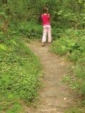 Rosafarbenes Mädchen im grünen Holz auf Spur Lizenzfreies Stockbild
