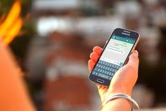 ROSARIO, ARGENTINA - 8 DE NOVEMBRO DE 2017: Menina com smartphone e um whatsapp na tela Fotografia de Stock Royalty Free