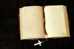 Rosario y libro vacío de las paginaciones Fotografía de archivo
