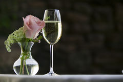 Rosarose mit einem Glas Weißwein. Stockbilder
