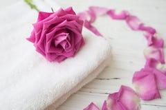 Rosarose und -blumenblätter auf weißem Tuch Lizenzfreies Stockbild