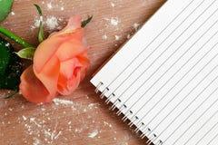 Rose und Notizbuch auf dem hölzernen Hintergrund lizenzfreie stockbilder