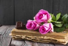 Rosarosen und -schokolade des alten Buches auf einem dunklen hölzernen Hintergrund Stockbilder