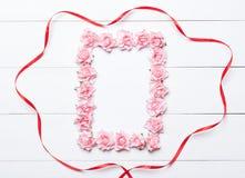 Rosarosenrahmen mit rotem Band über weißem hölzernem Hintergrund Lizenzfreies Stockfoto