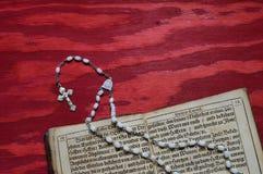 Rosary με το παλαιό αρχαίο βιβλίο στο κόκκινο ξύλο Στοκ εικόνες με δικαίωμα ελεύθερης χρήσης